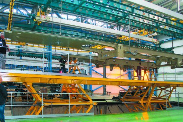Operazioni di scarico di un telaio pronto per essere inviato alla finitura. Si notino le dimensioni, in rapporto agli addetti.