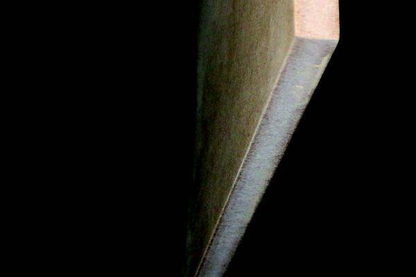 Un pannello di MDF già appeso alla bilancella in ingresso nel forno con pannelli catalitici IR per il pre-riscaldo a 80 °C. Si nota la leggera levigatura effettuata sui bordi.