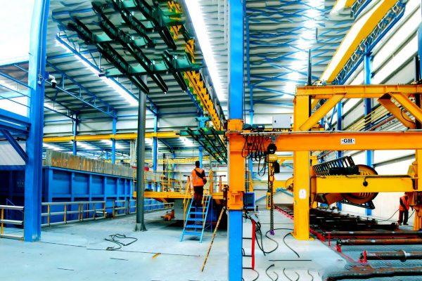 La zona di trasferimento dei telai al trasportatore aereo (mediante piattaforma elevatrice) e successivo scambio dalla linea aerea alla linea a vasche sia dei telai, sia delle sottobarre dei componenti e dei pezzi provenienti dall'esterno
