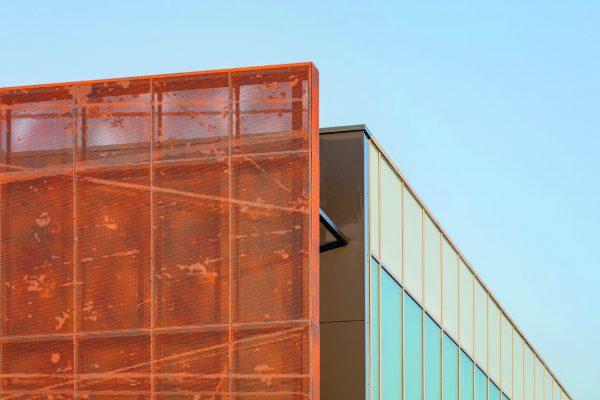 Un dettaglio dei moduli di alluminio forato che compongono la facciata del Patinoire. Il colore caratteristico è ottenuto con una verniciatura a polveri, colore Effervescent Earth della collezione Patina di Adapta Color.