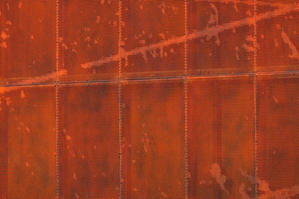 Un dettaglio dei pannelli di alluminio con fori di diametro differente, e striature che ricordano le scie create dai pattini sul ghiaccio.