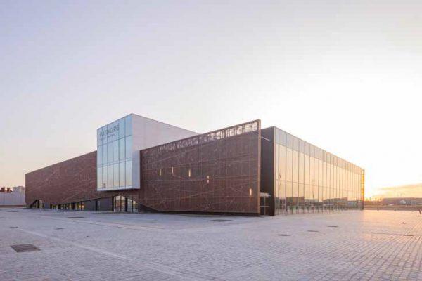 """Il """"Patinoire"""" di Dunkerque, nel nord della Francia, è un edificio per attività sportive, il pattinaggio su ghiaccio. Inaugurato all'inizio di settembre 2019, è stato progettato dall'Agence Chabanne, studio di architettura e ingegneria fondato da Nicolas Chabanne. É caratterizzato dalla facciata di pannelli di alluminio leggero perforato verniciati a polvere con finitura e colore caratteristici (collezione Patina Adapta Color, colore Effervescent Earth)."""