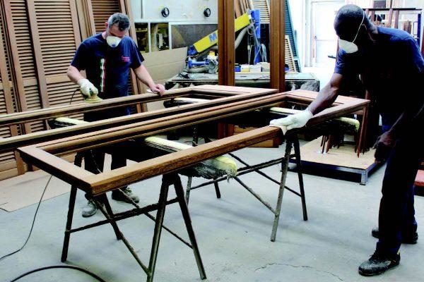 Levigatura di serramenti, i pezzi vengono preparati per le operazioni di restauro.