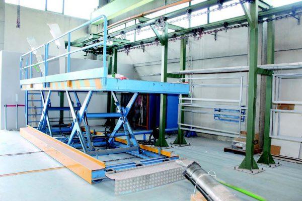 La soluzione automatica adottata per l'appensione di pezzi di grande dimensione sull'impianto. La paittaforma montacarichi a riposo e in fase di sollevamento.