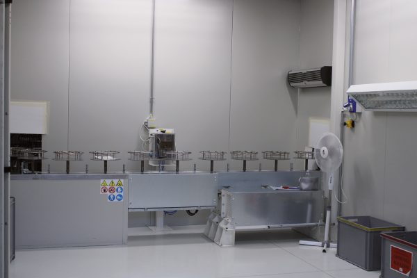 All'interno delle cabine di verniciatura: rispettivamente la postazione di soffiaggio antistatico dei pezzi e il nastro trasportatore.