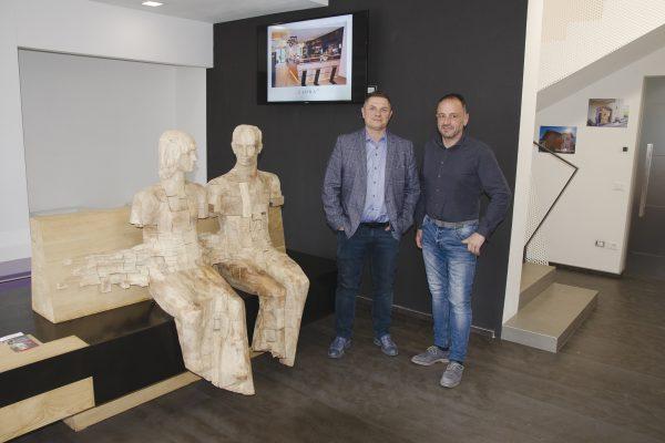 Markus Trebo e Massimo Zadra nell'ingresso dello stabilimento, dove è stata posizionata una scultura costruita con legno di scarto.