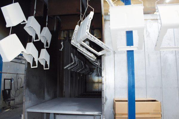 """Un """"tour"""" nelle varie fasi dell'impianto di verniciatura: postazione di carico e scarico dei pezzi; passaggio nel tunnel di pretrattamento; applicazione con post-ritocco; polimerizzazione in forno a 180 °C."""