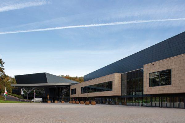 """La facciata dell'edificio è costruita con il sistema a secco costituito da pannelli rettangolari con angoli piegati a """"cassetta"""", di diversa dimensione."""