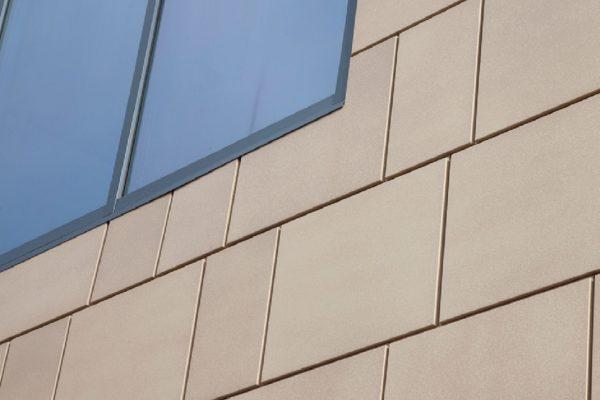 """Il dettaglio della facciata. Si noti l'aspetto """"materico"""" irregolare della finitura chiara, resa ancor maggiormente interessante dalla resa opaca della vernice e la irregolarità della pietra naturale. Come ben evidenziato nel campione di Patina Stone Collection in dettaglio, la finitura non è """"imitativa"""" ma """"evocativa"""", cioè ricorda nell'aspetto opaco, nel colore e nella irregolarità superficiale la pietra di riferimento."""