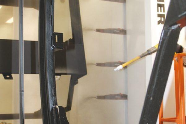 Dettaglio della cabina automatica di verniciatura a polveri dotata di due reciprocatori con sei pistole ciascuno