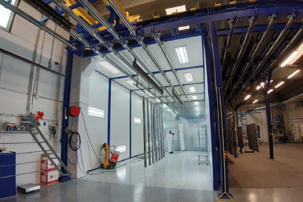 """L'impianto di verniciatura a polveri è organizzato ad """"isole"""" con trasportatore verticale."""