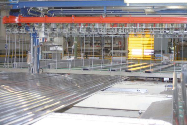 Un esempio dei ganci agganciati al convogliatore, cui vengono appesi i profili d'alluminio da verniciare