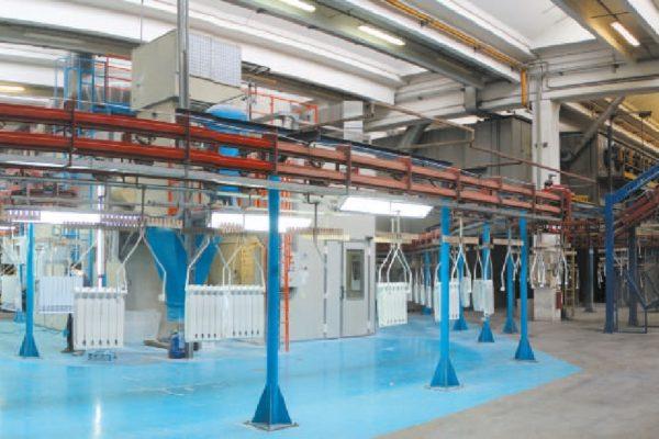Vista generale dell'impianto di verniciatura, che collega via trasportatore aereo i reparti di trasformazione della lega d'alluminio in radiatori (a destra) e quello di controllo qualità, imballaggio e preparazione delle spedizioni dei radiatori finiti (a sinistra).